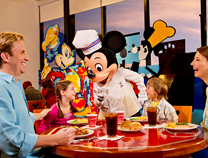 Chef Mickey talking to two children at the dinner table while the parents laugh