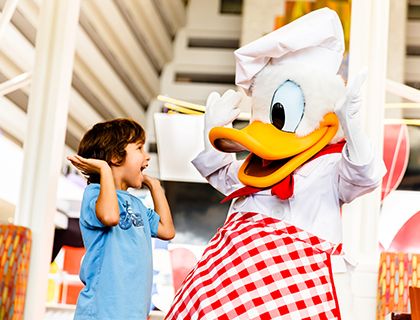 Donald Duck and a boy raising their hands for a double high five