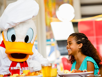 Laughing girl and Donald Duck dressed as a chef at Character Breakfast