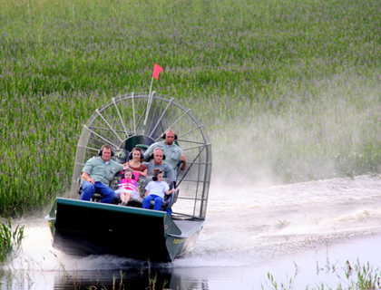 Front view of a small airboat with tourists speeding through the Everglades