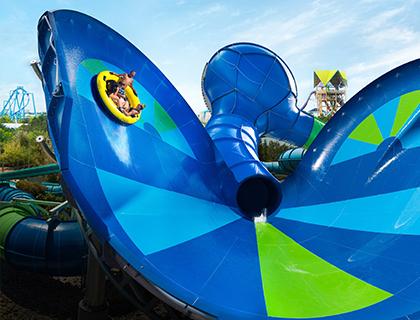 Seven people racing down the Taumata Racer Slides at Aquatica