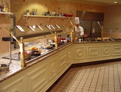 Long breakfast buffet counter and a chef working