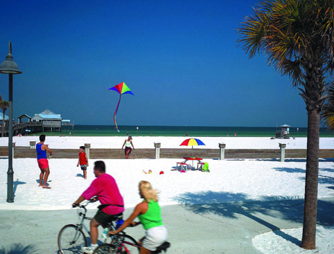Couple cycling and a father with child flying a colourful kite on the sand on Clearwater Beach
