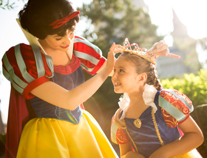 Snow White placing tiara on little girl dressed as a Disney Princess