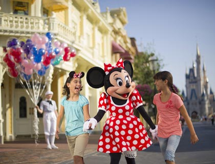 Minnie Mouse holding hands with two girls at Walt Disney World