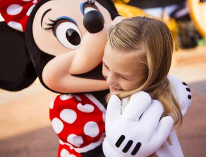 Minnie Mouse giving little girl a kiss at Walt Disney World