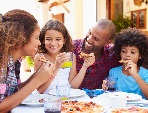 Happy family of four eating pizza at a restaurant