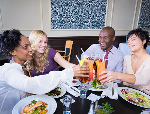 Four friends happily raising glasses of orange cocktails at the dinner table over plates of food