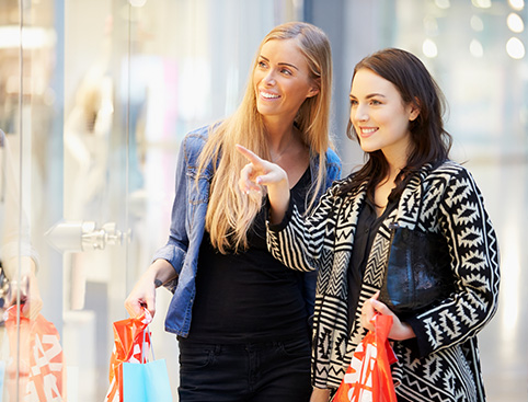 Two women window shopping - one pointing at the items on show