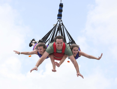 Man and two girls laugh as they dangle in the air on the Sky Coaster at Fun Spot Kissimmee