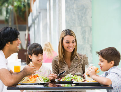 Family of four, sitting at a table, ready to tuck into large portions of food
