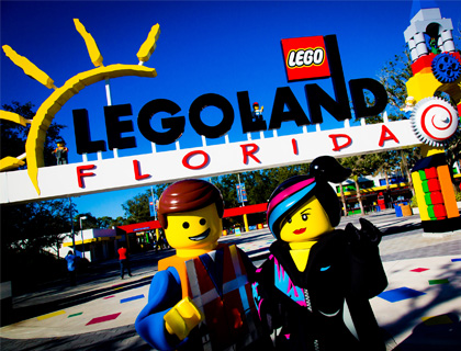 Emmet and Wyldstyle posing at the entrance of LEGOLAND Florida with smug smiles