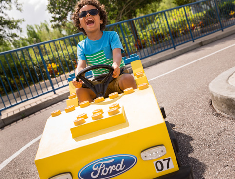 Curly boy with sunglasses laughing out loud while driving a yellow Lego car at the LEGOLAND City Driving School
