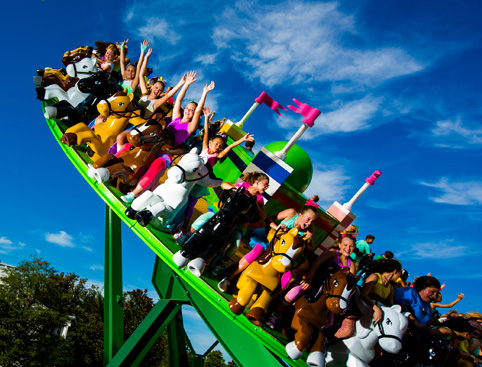 Children sitting on ponies on the Castle Hill roller coaster waving their hands in the air