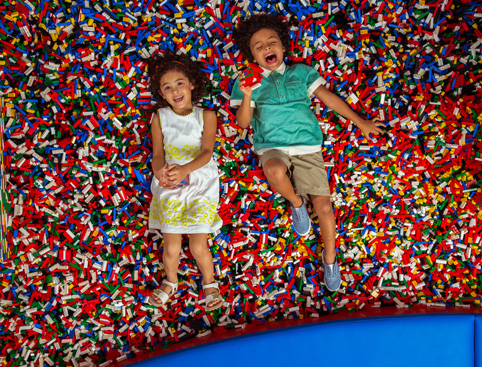 A little boy and a little girl lying on their backs on top of a huge pile of Legos laughing