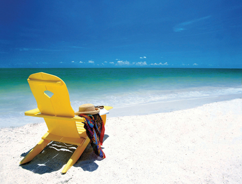Yellow long chair on the sand of Clearwater Beach, facing the clear blue water, with a women's hat and a scarf lying on it