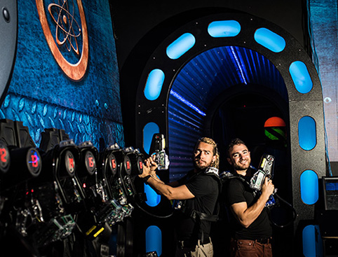 Two guys posing back to back with laser guns at the Lazer Tag Experience at WonderWorks